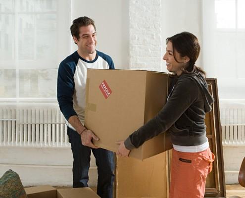 Couple carrying cardboard box
